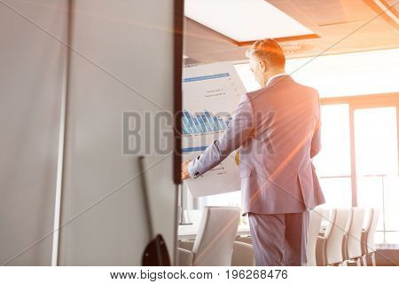 Rear view of businessman analyzing graph on chart in board room