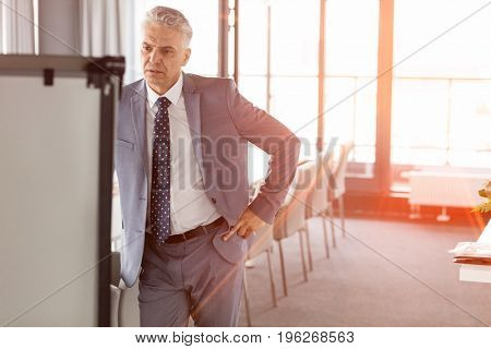 Mature businessman looking at whiteboard in meeting room