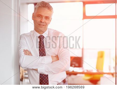 Portrait of mature businessman with arms crossed leaning in doorway at office