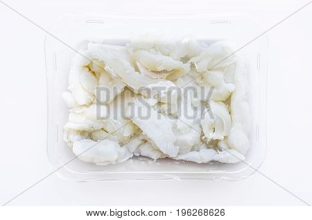 Packed tray with desalted slices of codfish. Isolated over white background