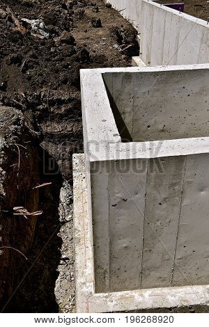 The foundation and footing from poured concrete into forms in a construction project with no basement