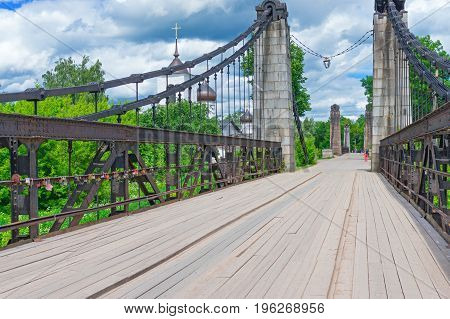 Wooden cable-stayed bridge with metal railing and stone colo