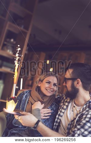 Young couple in love sitting in a cafe boyfriend surprises his girlfriend with a fireworks birthday muffin