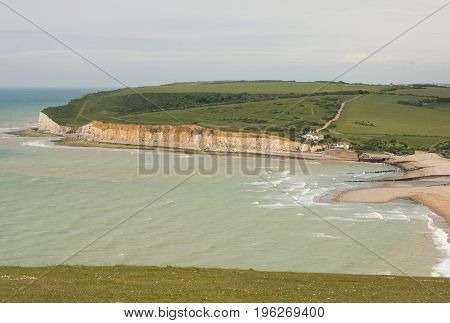 River Cuckmere shingle beach and chalk cliffs at Cuckmere Haven near Eastbourne East Sussex England. With unrecognizable people on beach