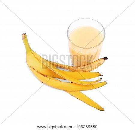 Freshly squeezed juice from tropical and sweet banana, isolated on a white background. The glass full of banana drink. The yellow banana peel near the smoothie. Nutritious fruits.