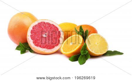 A delicious, juicy and ripe group of citrus fruits, isolated on a white background. Bright yellow lemon, red grapefruit cut in half. Sweet oranges with green leaves of mint.