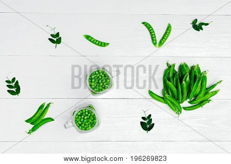 Full glass jar with fresh green peas on white wooden background top view. Bio healthy food. Green peas in jar pods and pea leaves on wooden table