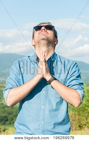Young Male With Sunglasses Praying Outside