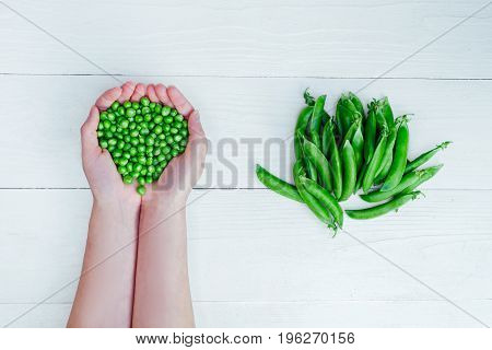 Woman's Hands Holding Green Peas On White Background Near Pods Of Green Peas, Close-up