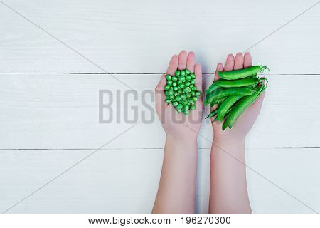 Woman's Hands Holding Green Peas And Pods On White Background, Free Space, Close-up
