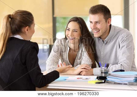 Happy couple talking with a real estate agent at office