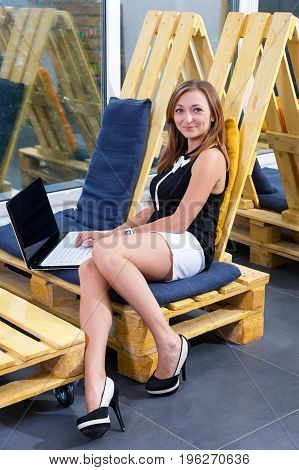 Young businesswoman working with new startup project using laptop computer in modern loft. Casually dressed female freelancer at coworking space