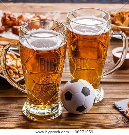 Appetizers and beer on the table for the football party and watch the football match.