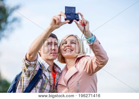 Couple taking a selfie on camera in park