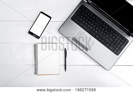 Top View On White Wooden Table With Open Blank Laptop Computer, Cell Phone, And Empty Diary With Pen