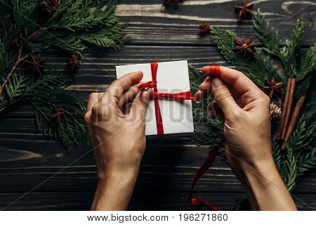 Hands Wrapping Christmas Present With Red Ribbon On Stylish Wooden Background Flat Lay With Green Br