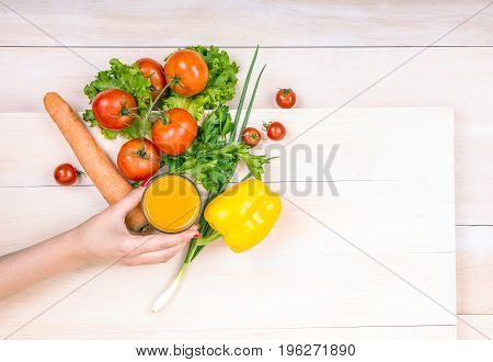 Woman holding a transparent glass of orange juice. Close-up vegetables on a bright background. Tomatoes and lettuce laying on a wooden table. Tasteful healthful carrots, onions.
