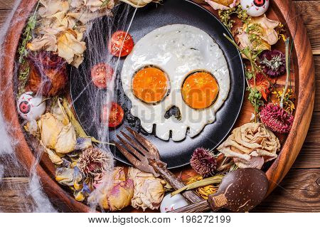 Fried eggs in the shape of a skull and fresh tomatoes. Breakfast in Halloween decorations. Top view