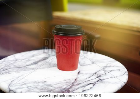 Red paper disposable cup of coffee to takeaway on marble table in garden outside cafe. Breakfast morning on air
