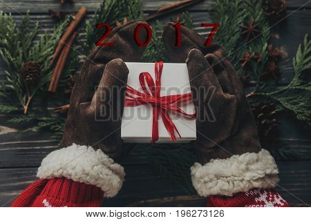 Hands In Vintage Gloves Holding Christmas Present With Red Bow On Stylish Rustic Wooden Background W