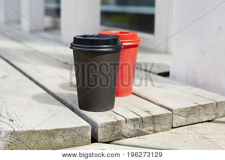 Red and black paper cups of coffee to takeaway on wooden floor outside the cafe. Breakfast morning on air