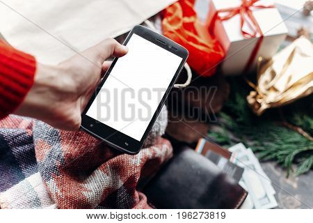 Christmas Shopping Concept. Hand Holding Phone With Empty Screen . Seasonal Sale. Rustic Background