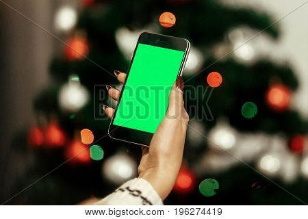 Stylish Woman Holding Phone And Showing Empty Screen At Christmas Tree Lights. Seasonal Greetings. C