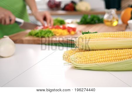 Close up of woman's hands cooking in the kitchen. Corn on the cob.