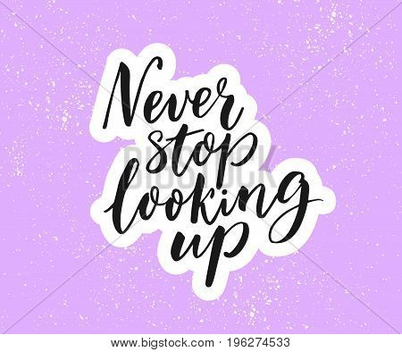 Never stop looking up. Inspirational quote, brush calligraphy on purple background