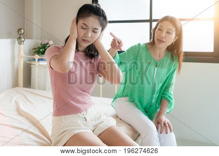 Beautiful Asian mother is scolding her teenage daughter girl is ignoring her mother.