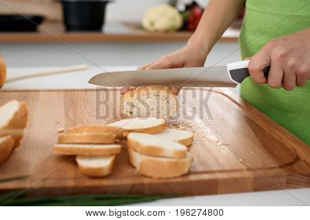 Close up of woman's hands cooking in the kitchen. Housewife slicing white bread. Vegetarian and healthily cooking concept.