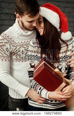 Handsome Romantic Man Kissing & Hugging Emotional Brunette Woman In Reindeer Sweater And Santa Hat A