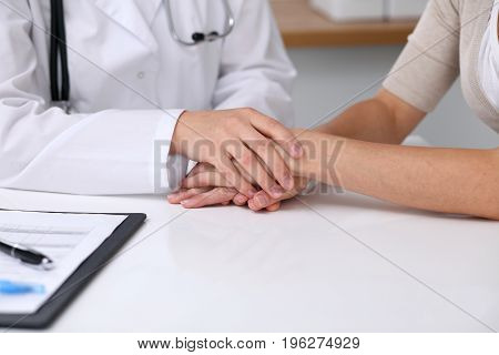 Close up of a doctor reassuring her female patient while sitting at the desk. Medicine, help and health care concept.