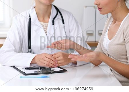 Close up of doctor and patient sitting at the desk while physician pointing into medical form hystory. Medicine and health care concept.