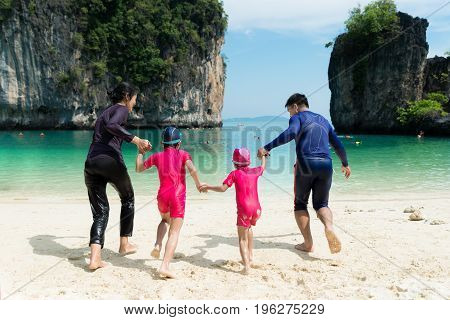 Photo of Asian happy family running down the beach on summer in Phuket Thailand. Summer Travel Vacation and Holiday concept.