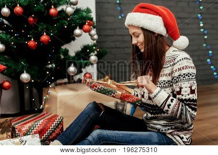 Happy Woman Opening Christmas Present Box. Girl In Sweater With Deers And Wearing Santa Hat In Festi