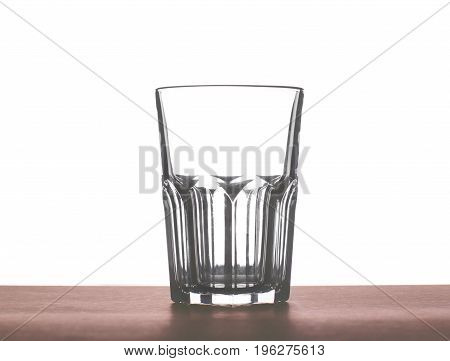 A big empty transparent water drinking glass for water, juice or milk on a dark brown wooden table, isolated on a white background.
