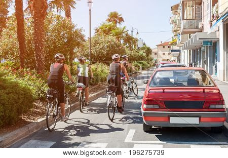 A group of cyclists rides around town on a Sunny day on the paved road.