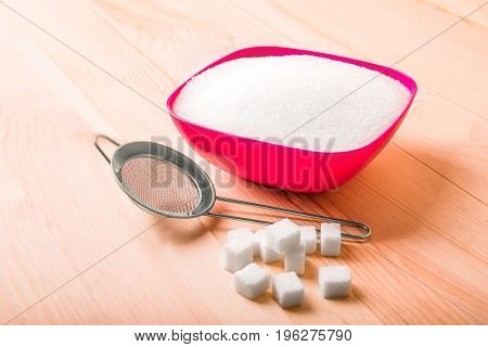 Sweet and tasty sugar in an attractive plastic pink box on a large light brown table, isolated on a white background. A small sieve and cubes of white sugar are on a light brown wooden table.