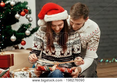Happy Cozy Family Moments In Winter Holidays. Stylish Excited Couple Opening Presents At Decorated C