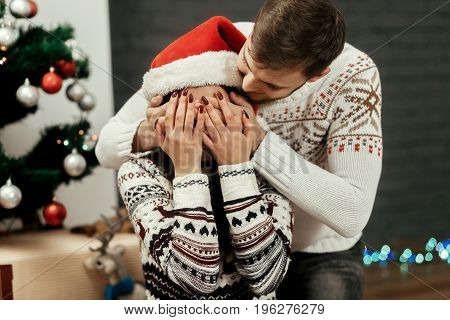 Happy Family Couple, Handsome Man Preparing A Christmas Present Surprise For Beautiful Woman In Sant