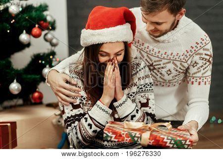 Happy Boyfriend And Girlfriend Couple Near Christmas Tree, Beautiful Woman In Santa Hat Emotional Re