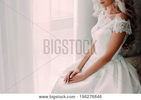 Charming bride blonde with curly hair sits near the window. Morning before the wedding ceremony. A bride is awaiting her groom. Close-up