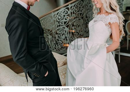 Happy and emotional moment of the first meeting of groom and bride on their wedding day. Wedding concept. Groom and bride are laughing to each other