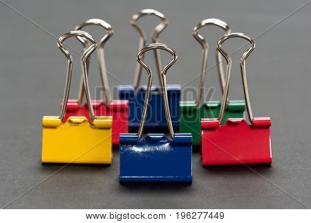 Colored binder clips on a gray background