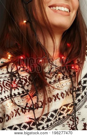 Stylish Woman In Christmas Lights Closeup. Posing And Smiling In Festive Holiday Time. Joyful Moment