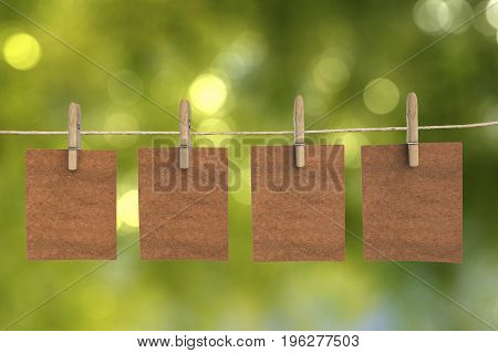 four brown blank papers hanging on clothpins