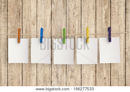 five blank papers hanging with cloth pegs
