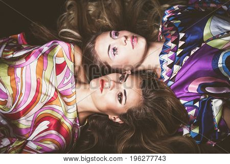 beautiful two young women with long blonde hair beauty fashion portrait lie down in colorful silky dress studio shot