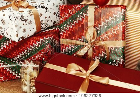 Christmas Presents Wrapped In Colorful Gift Boxes And Golden Ribbons, Lying On The Wooden Floor Back